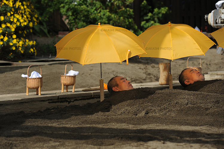 Men taking a sand bath in Beppu.