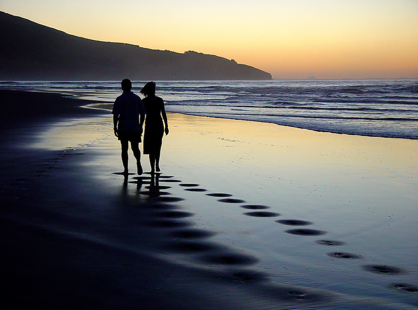 Couple walking on a beach at sunset.