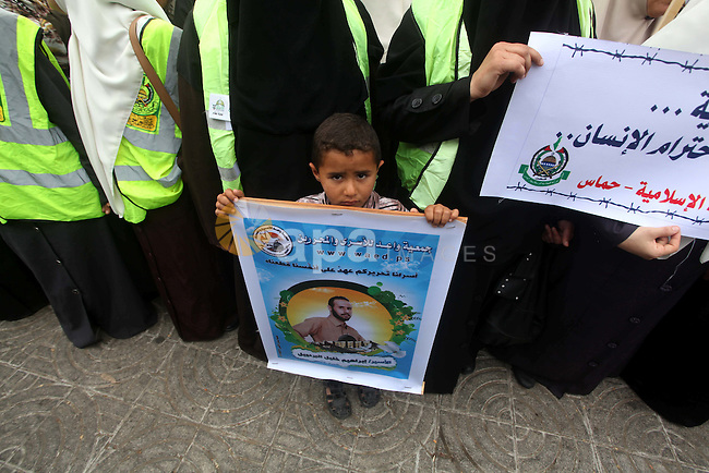 A Palestinian child holds pictures of incarcerated relatives in a rally to show solidarity with prisoners held in Israeli jails, in Gaza City May 14, 2012. One in three of the 4,800 Palestinians serving time in Israeli jails began refusing food on April 17 in protest against their detention without trial and to demand better conditions, like an increase in family visits and the ending solitary confinement. Photo by Ashraf Amra