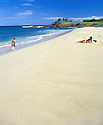 Man with snorkeling gear and woman sunbathing at Kepuhi Beach, Molokai, Hawaii. .