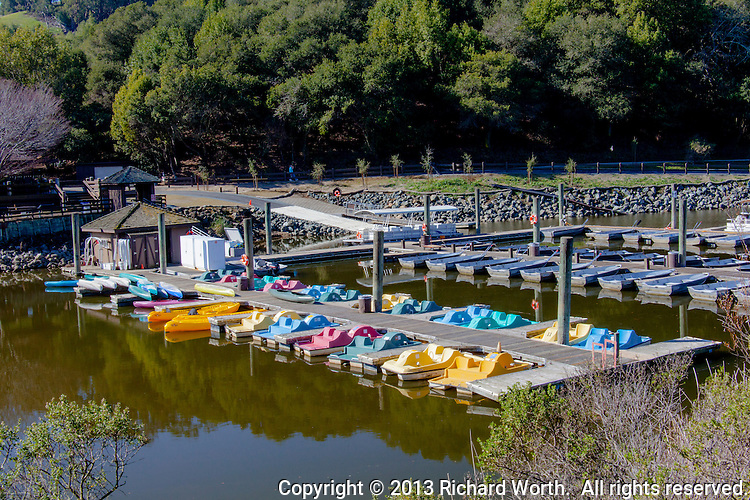 Bright colored pedal boats, kayaks and canoes, all for rent, brighten the pier at Lake Chabot Regional Park in Castro Valley, California.