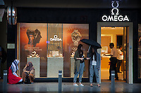 Switzerland. Canton Bern. Interlaken. Rainy Sunday afternoon. Omega watches shop. Tourist from Asia and the Middle East. Two young women from Asia ( China, Japan) protect themselves under an open umbrella. Two arabic women kneel down and and talk together. Both women have covered their hair with a hijab. Customers shopping. A giant marketing campaign with an Omega watch and the face of Michael Phelps. Michael Phelps is an American competitive swimmer and the most decorated Olympian of all time with a total of 28 medals. 31.07.2016 © 2016 Didier Ruef