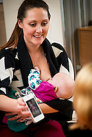 A mother breastfeeds her baby while showing a picture on her mobile phone to another mum at a drop-in breastfeeding support centre.<br /> <br /> Image from the breastfeeding collection of the &quot;We Do It In Public&quot; documentary photography picture library project: <br />  www.breastfeedinginpublic.co.uk<br /> <br /> Hampshire, England, UK<br /> 13/03/2013<br /> <br /> &copy; Paul Carter / wdiip.co.uk