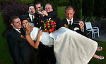 A bride and groomsmen joke around as they pose for group photos following the ceremony.
