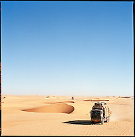 Sahara desert, Libya-Chad, November/December 2004..Every week, a convoy of 40 privately owned Libyan trucks loaded by the WFP with about 1000 metric tons of western food aid cross 2500 km of deep desert across Libya and Chad to reach more than 200 000 refugees from Darfur in camps near the Sudanese border. The convoy crawls across a patch of sand dunes under the blazing Sahara sun...