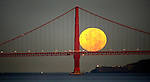 The full moon set seemingly on the deck of the Golden Gate Bridge during Wednesday commute hour (6:35am) seen from Treasure Island on September 26, 2007..
