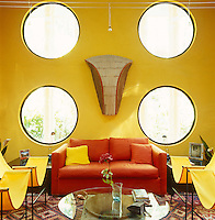 The brightly coloured living room wall of Edward James' former home is punctuated by four circular windows