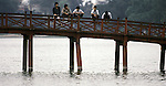 Young men sit on a bridge spanning the Lake of the Restored Sword in Hanoi, North Vietnam.  (Jim Bryant Photo).....