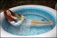 BNPS.co.uk (01202)558833<br /> Pic: AnnaGrayson/BNPS<br /> <br /> 'Ophelia in the Hot Tub' after Millais.<br /> <br /> A photographer is taking the art world by storm with her modern take on the Old Masters - using her long suffering husband as a model.<br /> <br /> Anna Grayson's pastiche photos of greats like Leonardo Da Vinci, Jan Van Eyck and Botticelli are proving a hit with art fans and one of her works was even displayed at London's prestigious Royal Academy.<br /> <br /> Calling upon friends, family and fellow artist husband Des Maxwell Clark to serve as models, Grayson uses natural light and modern props including wigs, blankets, a selfie stick, a Barbie doll and even an inflatable hot tub for her unusual work.<br /> <br /> The quirky pictures will all seem vaguely familiar to anyone with a basic knowledge of famous art, but each has a modern twist - for example Van Eyck's Arnolfini couple are distracted on their mobile phones.<br /> <br /> Grayson has a collection of her work on permanent display at the Artizan Gallery in Torquay and a new exhibition opening at Words and Pictures Gallery in Teignmouth on May 26.