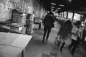 "Pedestrians walk past the cardboard ""homes"" of homeless people in the underpass of a Shinjuku street, Tokyo, Japan."