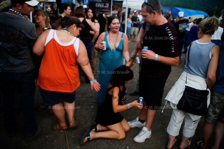 A woman falls to the ground at the Testicle Festival at the Rock Creek Lodge in Clinton, MT.  The Rock Creek Lodge in Clinton, MT, has hosted the annual Testicle Festival since the early 1980s.  The four day festival and party revolves around the consumption of so-called Rocky Mountain Oysters, which are deep-fried bull testicles.