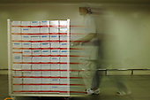 A pharmaceutical factory worker pushes a trolley of packaged drugs to the warehouse.. Royalty Free