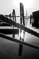 USA, Newport, RI - A shields class sailboat sails in the distance in the later afternoon sun past the end of the Bannister's wharf pier. (Black and White)