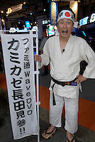 """Man dressed in martial arts gear advertising a Japanese magazine for console game players. The bandana says """"Kamikaze""""."""