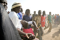 A young woman collapses due to the heat and excitement after her team won a volleyball match at the Twic Olympics in Wunrok, Southern Sudan.