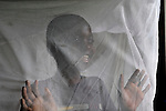 A girl looks out from under the bednet on her bed in the Mary Morris Orphanage, run by the United Methodist Church in Kamina, Democratic Republic of the Congo.