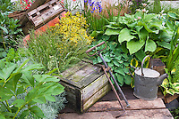 Rustic wooden boxes, antique watering can, old farm implements tools, hostas, Weigela, irises, herbs, ornamental grasses for a charming nice mix of garden plantings, using aged items from flea markets and yard sales
