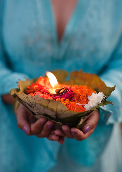 A woman makes a floral offering to the Ganges River at dusk in Rishikesh, Uttarakhand, India. The Ganges has long been considered a holy river by Hindus and is widely worshipped as the goddess Ganga.