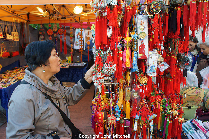 Woman looking at Chinese good luck charms at the night market in Chinatown, British Columbia, Canada