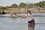 Maria Diaz throws a fishing net in a river near Santa Paula, a hot and isolated village in northwestern Nicaragua.