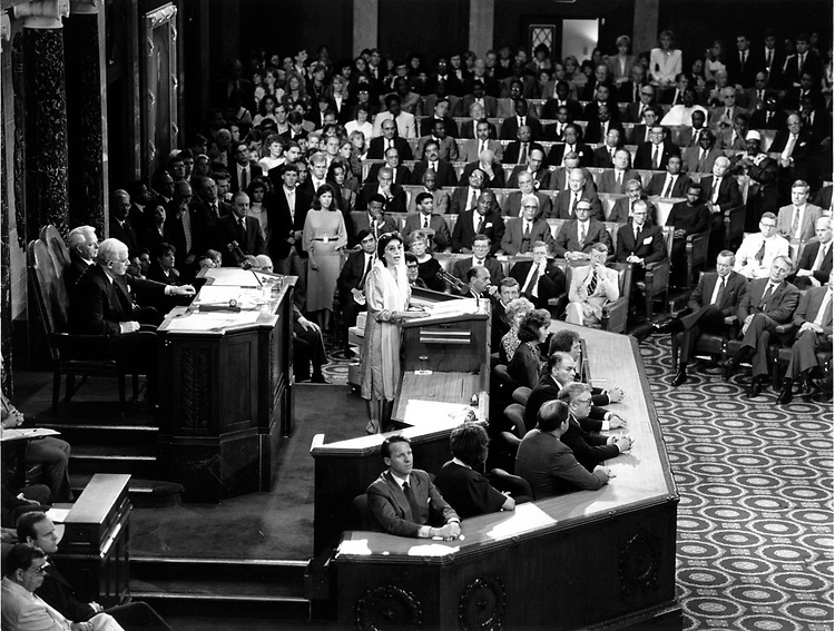 """This photo was taken in a Joint Meeting of Congress in the House Chamber on 7 June 1989.  Here Prime Minister of Pakistan Benazir Bhutto addressed Congress after being elected the first female Prime Minister from a Muslim state in December of 1988.  At the age of 35 in 1989, she recognized the strong relationship between the United States and the Islamic Republic of Pakistan.  One of the more interesting and most notable points she addressed in her speech is the mutual desire for, """"a stable, independent and neutral Afghanistan, an Afghanistan where the people can choose their own system, their own government in free and fair elections.""""  This desire would be sought and eventually met in the years to come."""
