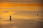 Two buoys on a golden sunrise reflected ocean, simulating an island.