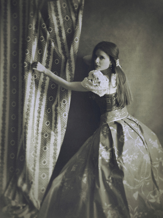 A monochromatic image of a woman in a victorian outfit, standing at a wall and touching a decorative curtain  with one hand, and her hair with another.