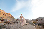 Beautiful woman in a formal gown expressing expansiveness in a wide opne desert landscape.