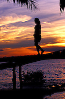 Woman walking on ramp from thatched hut on the ocean at sunset, Siargao Island, Philippines