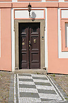 A pink building with a checkered path leading up to the front door in Prague, Czech Republic.