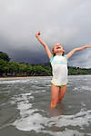 Central America, Costa Rica, Manuel Antonio. Young girl in water as storm approaches.
