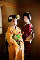 Yachiho-san, a geisha and Komomo, an apprentice maiko<br /> Kyoto, Japan, 2005. As geisha, Yachiho-san and Komomo&rsquo;s job is to entertain clients with their elegant beauty and talents. Here in their traditional giesha house or okiya, dressing for the evening is time consuming. As their kimonos can weigh up to thirty pounds and trail twenty-five feet in length the girls have a strong male dresser to help. Once becoming a geisha the maiko cuts her hair and then dons a wig instead of wearing this elaborate hairstyle with her own hair.