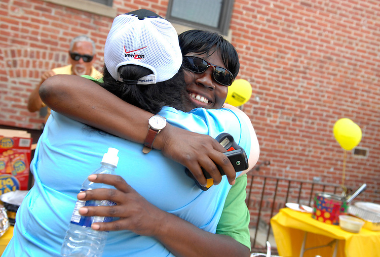 Former student Sandra Johnson, right, hugs program director Nicole Lubar for the Washington Literacy Council, during a cook out to honor graduates and their tutors, at their office in Adams Morgan.