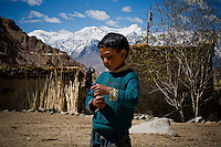 A Ladakhi boy plays in the fields on 2nd June 2009 as his relative looks out from the family house, one of only 3 houses scattered on one side of the valley of Ulley. His relatives run a Home stay program. Ulley is a scattered village of only 5 houses, one school, 38 people, 4 school children, and 4 pet dogs. The village is not accessible by road. The homestay program is managed by 'Snow Leopard Conservation Organisation', an NGO that helps families in the mountains that face constant snow leopard attacks on their livestock.  Photo by Suzanne Lee
