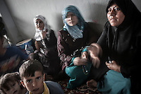 Syrian refugees await in a covered parking area as they take remporary shelter at the Azaz border check point settled by FSA for those who flee from army shelling in the northern villages of Aleppo province. Due the flowing of thousands of Syrian refugees who have crossed into Turkey fleeing from aircraft bombing, the turkish government have closed the border leaving dozens of hundreds of families stuck along the border areas, mostly of them children and women.