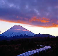 Snow covered Mount Ngauruhoe in Tongariro National Park at sunrise with  storm clouds-New Zealand