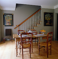 The breakfast room is painted grey with a pair of citrus tree paintings and a small wooden table with chairs