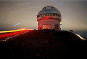 Stars move overhead and trails from tail lights move over the roads near the Gemini North observatory on the 13,700 foot high peak on Hawaii's Big Island. The dome houses one of the world's largest and most advanced telescopes.