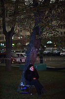 Moscow, Russia, 28/10/2011..An old woman shelters under a tree on Ploschad Revolutsii while watching the Bolshoi Theatre reopening gala on giant outdoor video screens. The theatre had been closed since 2005 for reconstruction work that cost some $700 million.