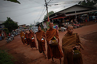 """Buddhist monks collect alms in Sam Phrao, a village designated as """"Red Shirt Village of Democracy"""" near Udon Thani in the northeastern Thailand June 27, 2011. The red shirts, supporters of ousted premier Thaksin Shinawatra, have been branding hundreds of villages as red to rally behind Thaksin's sister, Yingluck, who is leading the opposition ahead of July 3 general elections.   REUTERS/Damir Sagolj (THAILAND)"""