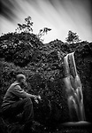 Long exposure of a man watching a waterfall on the Isle of Skye.
