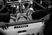 Young men, supposed gang members, lie handcuffed in the Police pick-up truck in San Salvador, El Salvador, 19 May 2011. During the last two decades, Central America has become the deadliest region in the world that is not at war. According to the UN statistics, more people per capita were killed in El Salvador than in Iraq, in recent years. Due to the criminal activities of Mara Salvatrucha (MS-13) and 18th Street Gang (M-18), the two major street gangs in El Salvador, the country has fallen into the spiral of fear, violence and death. Thousands of Mara gang members, both on the streets or in the overcrowded prisons, organize and run extortions, distribution of drugs and kidnappings. Tattooed armed young men, mainly from the poorest neighborhoods, fight unmerciful turf battles with their coevals from the rival gang, balancing between life and death every day. Twenty years after the devastating civil war, a social war has paralyzed the nation of El Salvador.