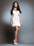 Beautiful smiling young black woman wearing short white dress isolated on gray background