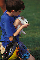 Young boy plays with pet rabbit at family style vacation campground.