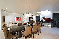 Large dining area is shown in modern open floorplan home with grand piano