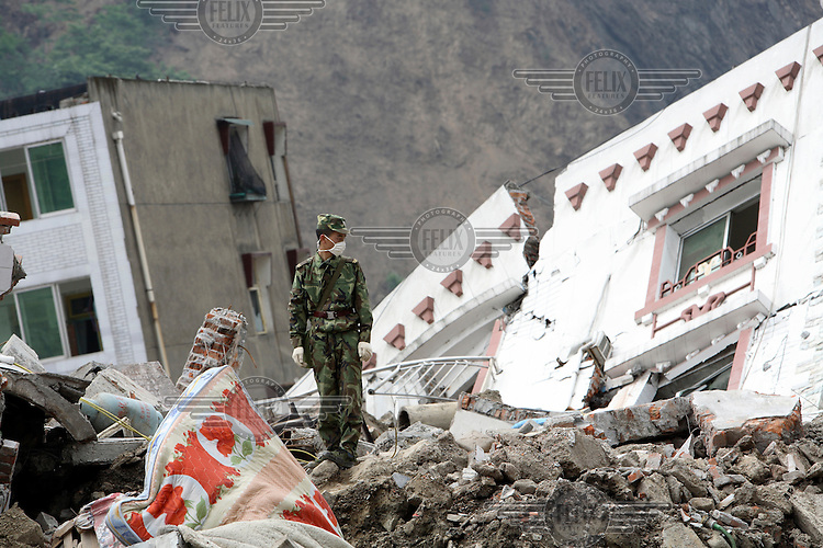 Soldiers search for signs of trapped life under collapsed buildings. An earthquake measuring 7.9 on the richter scale hit Sichuan on 12/05/2008.