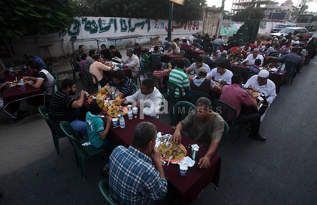 """Families of Palestinian prisoners in Israeli jails attend the collective breaking fast organized by the Association of """"Wa'ed"""" and funded by the Turkish relief """"IHH"""" in front of the Red Cross headquarters during the holy month of Ramadan, in Gaza City on 30 July 2012. Photo by Ashraf Amra"""