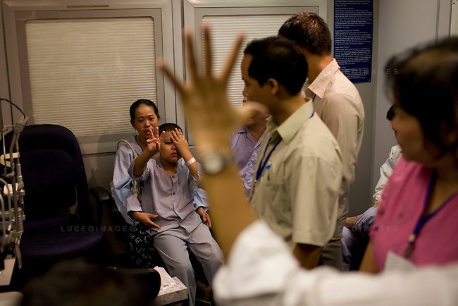 Doctors watch as they test 11-year-old Hung Nguyen's vision while sitting on his mother Binh Vo's lap following his glaucoma surgery at the ORBIS Flying Eye Hospital on Wednesday, April 16, 2008. Kevin German /  kevin@kevingerman.com..ORBIS Flying Eye Hospital brought doctors, nurses and specialists from all over the world to Ho Chi Minh City, Vietnam from April 7-18, 2008.  The ORBIS program contributed to the efforts of Ho Chi Minh City Eye Hospital in fighting avoidable blindness by educating local ophthalmologists to diagnose and manage pediatric blindness, retinal disease, oculoplastics, and blindness due to glaucoma.