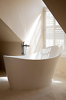 The master bathroom is decorated in neutral tones and features a stylish free standing bath in the centre of the room.