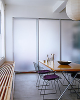 The opaque glass sliding screens in this dining room furnished with Bertoia chairs and a George Nelson table open up to reveal the den